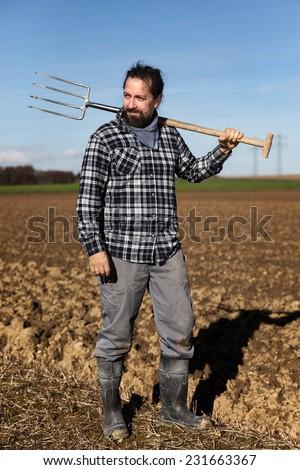 a Portrait of a european Farmer with a pitchfork - stock photo