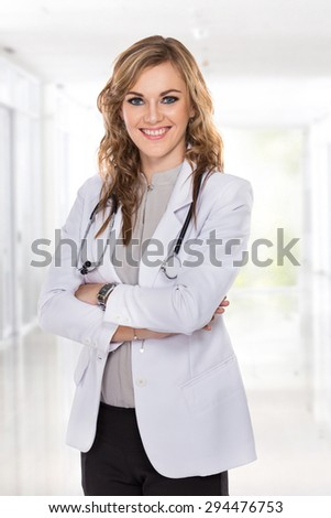 A portrait of a Female doctor standing with her arms crossed and smiling - stock photo