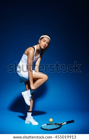 A portrait of a female tennis player with racket and ball aside in studio - stock photo
