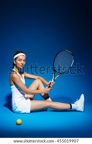 A portrait of a female tennis player with racket and ball sitting on floor in studio - stock photo