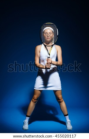 A portrait of a female tennis player with racket in front of herself - stock photo
