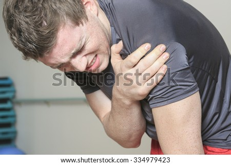 A Portrait of a fitness man reaching for his knee in pain - stock photo