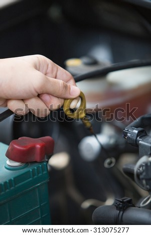A portrait of a hand Checking for engine oil on a car, machine related - stock photo
