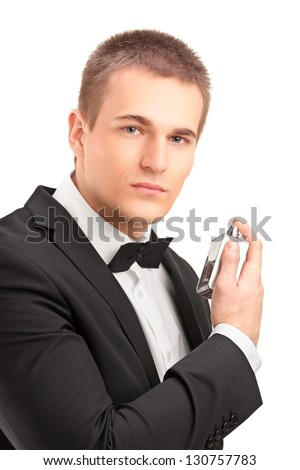 A portrait of a handsome male in black suit using parfume isolated against white background - stock photo