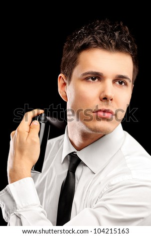 A portrait of a handsome model using perfume isolated against black background - stock photo