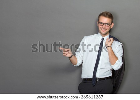 A portrait of a handsome young businessman wearing glasses and smiling pointing to copyspace - stock photo