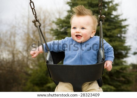 A portrait of a happy boy on a swing in a playground. - stock photo