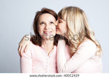 A portrait of a happy daughter kissing her mother - stock photo