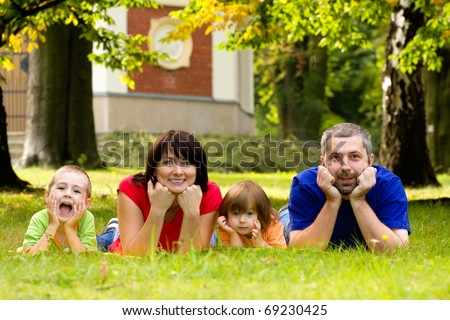 A portrait of a happy family lying on the grass in a park. - stock photo