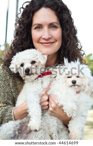 A portrait of a happy mature woman with her dogs outdoor - stock photo