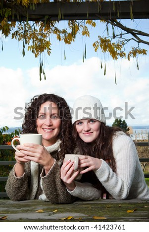 A portrait of a happy mother and daughter drinking coffee outdoor - stock photo