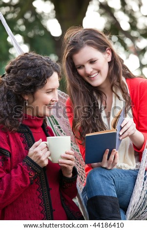 A portrait of a happy mother and daughter reading a book outdoor - stock photo