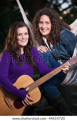 A portrait of a happy mother and daughter relaxing outdoor - stock photo