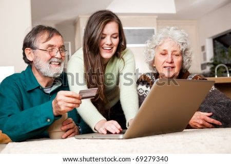 A portrait of a happy senior couple shopping online with the help from their granddaughter - stock photo