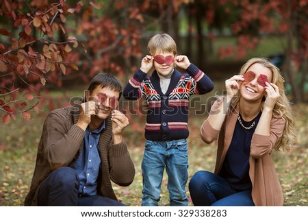 A portrait of a happy young family in autumn - stock photo