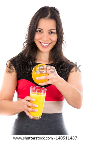 A portrait of a happy young woman squeezing and orange isolated on a white background - stock photo