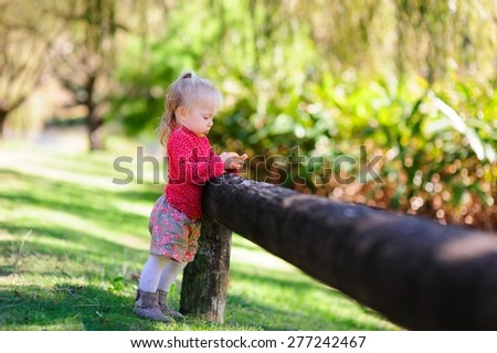 A portrait of a healthy child, an adorable baby or toddler girl peeling and holding a mandarin in a park on a nice sunny day - stock photo