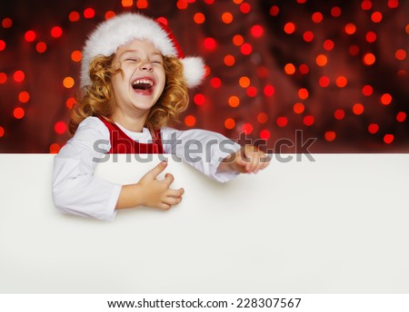 A portrait of a laughing cute little girl in Santa hat looking out from behind empty blank with her hands on it, isolated against Christmas glitter close up. Holidays concept. Invitation. Funny kids.  - stock photo