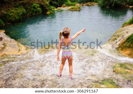 A portrait of a little girl at the cascades of Vanuatu wearing a colourful swimming suit standing with her back to the camera and pointing to something in front of her - stock photo
