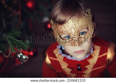 A portrait of a little handsome boy in masquerade costume and a carnival mask against the decorated Christmas tree. Fancy-dress ball. - stock photo