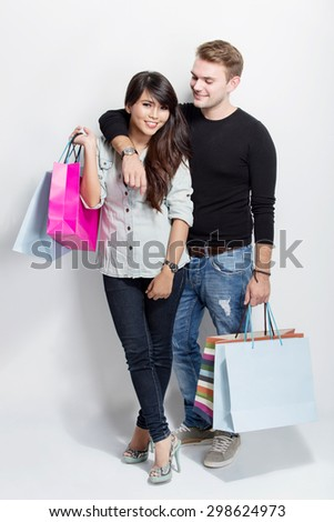 A portrait of a mixed couple standing holding shopping bag on white background - stock photo