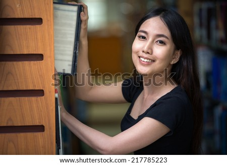 A portrait of a mixed race college asia student at campus in library - stock photo
