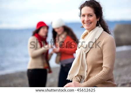 A portrait of a mother and her daughters on the beach - stock photo