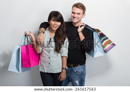 A portrait of a multicultural couple shopping together - stock photo