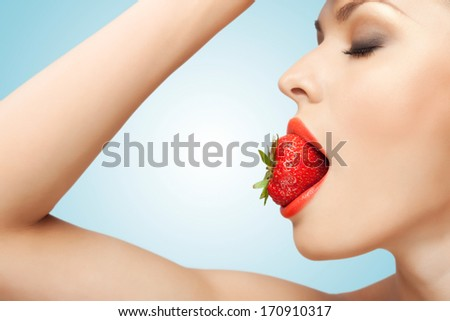 A portrait of a nude sexy woman holding a red-ripe strawberry in her mouth. - stock photo