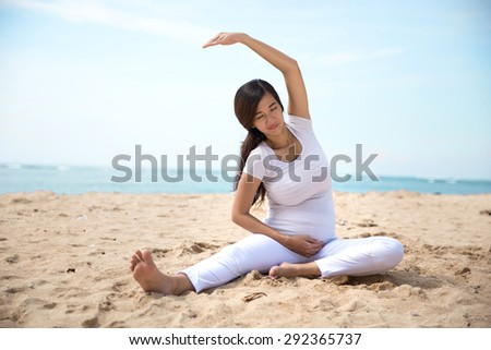 A portrait of a pregnant asian woman doing yoga in the sea shore - stock photo