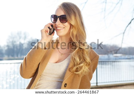 A portrait of a smiling beautiful woman talking on the phone - stock photo