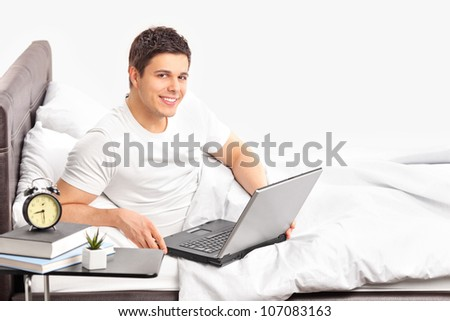 A portrait of a smiling man lying on a bed and working on a laptop - stock photo