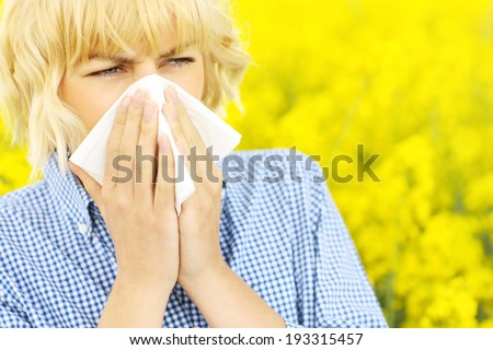 A portrait of a sneezing woman over a yellow field of flowers - stock photo