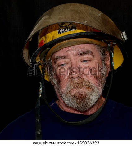A  Portrait Of A Sooty, Sweaty Fire Captain Looking Down In Despair - stock photo