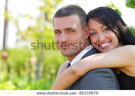 A portrait of a sweet couple in love embracing outdoors - stock photo