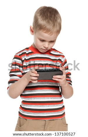 A portrait of a thoughtful boy with a smartphone - stock photo