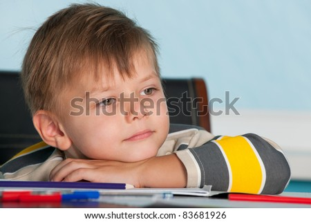 A portrait of a thoughtful little boy at the desk - stock photo