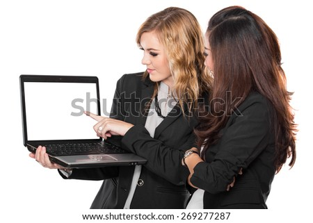 A portrait of a two businesswoman talking about something on the laptop, isolated - stock photo