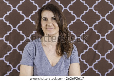 A portrait of a woman wearing a t-shirt smiling against a brown background - stock photo