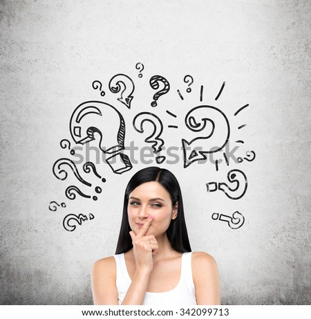 A portrait of a young artful brunette lady who is trying to find out a solution of some problem. The lady is in a white tank top. Different shapes of question marks are drawn on the concrete wall. - stock photo
