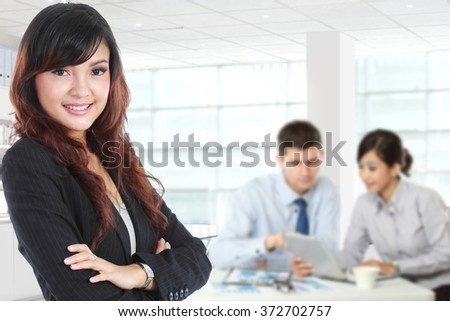 A portrait of a young asian businesswoman standing with her secretary behind - stock photo