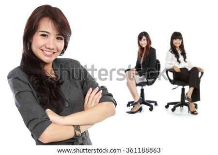 A portrait of a young asian businesswoman, with her team behind. isolated in white background - stock photo