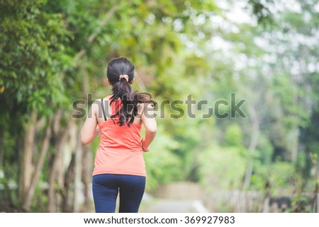 A portrait of a young asian woman doing excercise outdoor in a park, jogging - stock photo