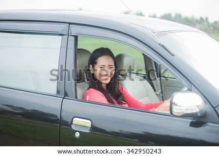 A portrait of a young Asian woman driving a car, smiling to the camera - stock photo