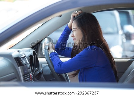 A portrait of a young asian woman on a ride, a car, frustrated - stock photo