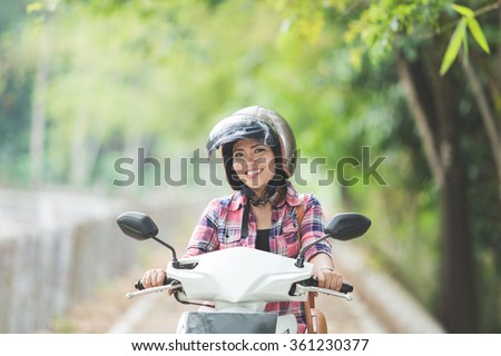 A portrait of a young asian woman riding a motorcycle in a park - stock photo