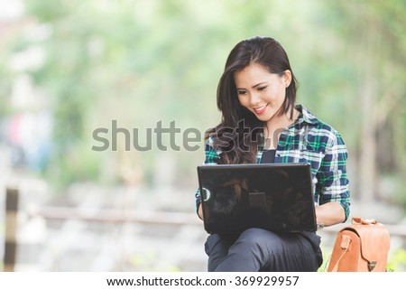 A portrait of a young asian woman using laptop while sitting on the park - stock photo