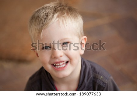 A portrait of a young boy smiling and looking at the camera.  The child looks relaxed and happy. - stock photo