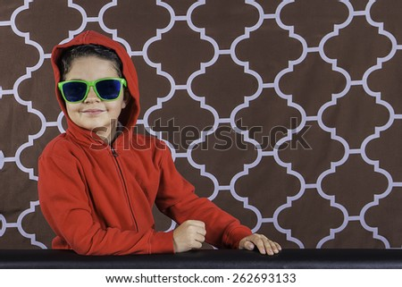 A portrait of a young boy smiling wearing a red hoodie and green sunglasses - stock photo
