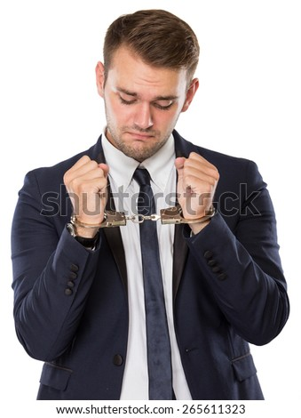 A portrait of a young businessman with handcuffs over hands - stock photo